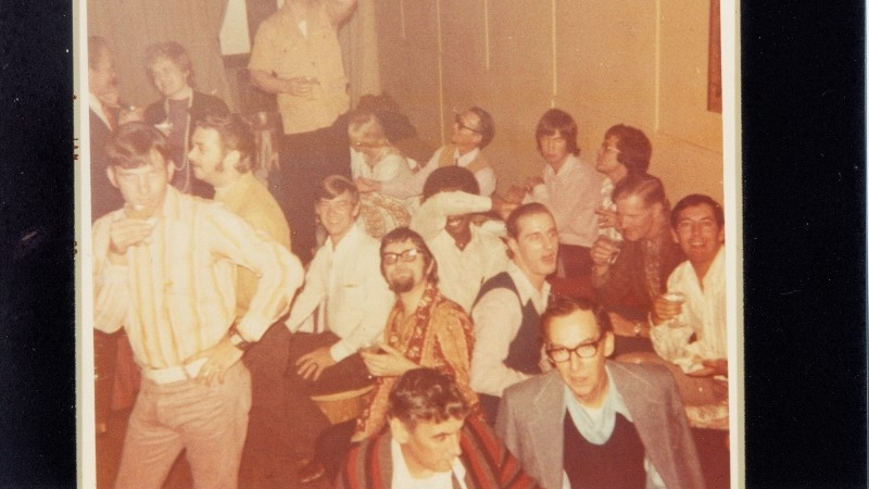 The Up Stairs Lounge crowd gathers in the bar's back theatre space. Patron Michael Scarborough poses, at lower left, with a drink. Image courtesy of Johnny Townsend (image supplied)